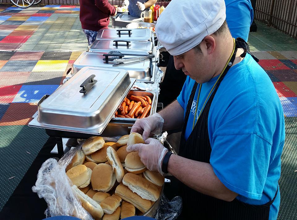 A man preparing hamburger and hotdog buns at an outdoor bbq.