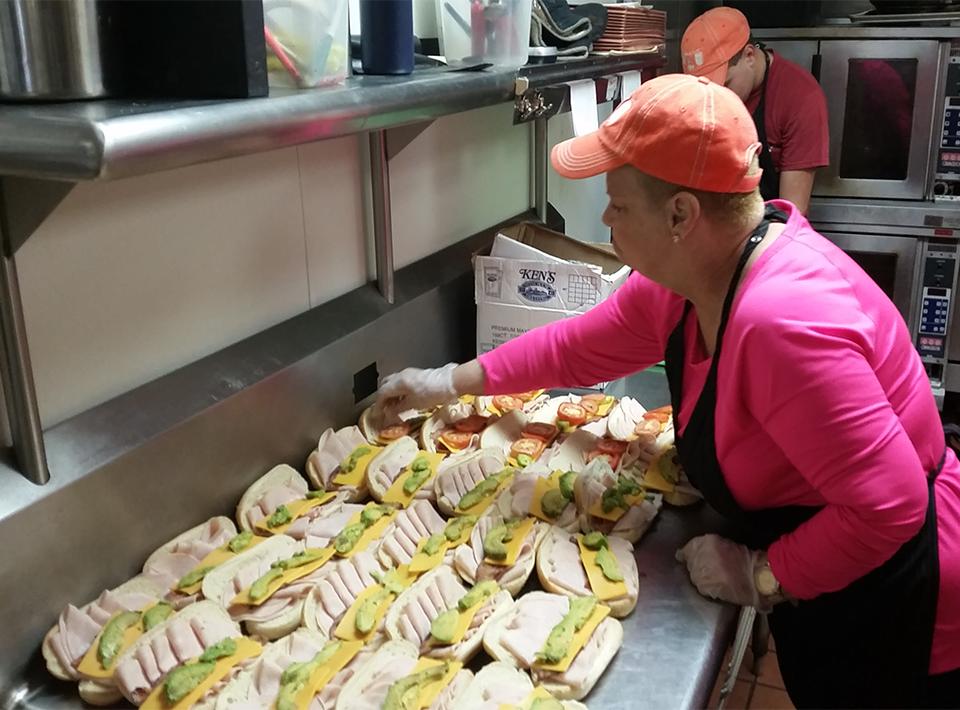Civitan Foundation member works in kitchen preparing sandwiches.